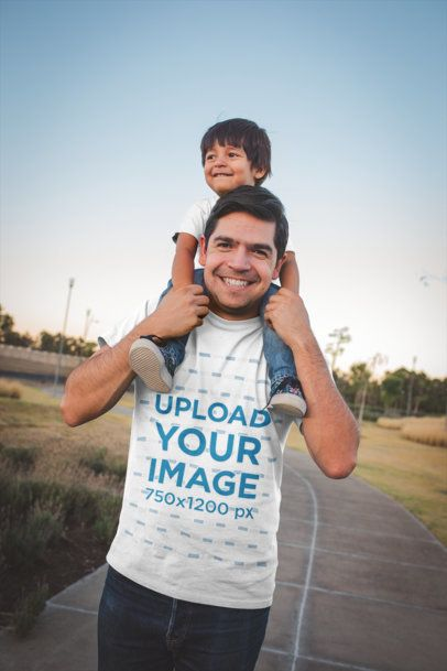 Dad Wearing a T-Shirt Mockup While Carrying his Son a20195