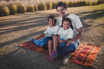 Dad with his Kids Wearing T-Shirts Mockup While Sitting at a Park a20198