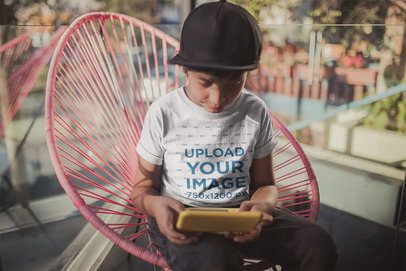 Little Kid Wearing a T-Shirt Mockup While Playing Videogames a20293