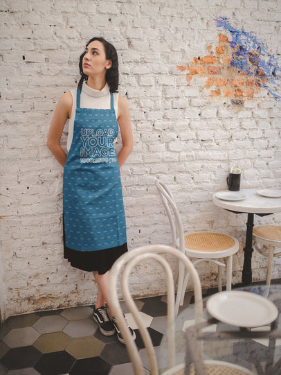 Girl Wearing an Apron Mockup Against a White Bricks Wall a19821