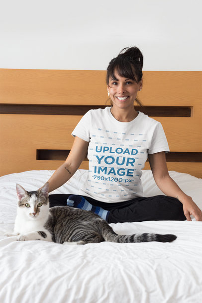 Portrait of a Happy Cat Owner Wearing a T-Shirt Mockup on Bed a18790