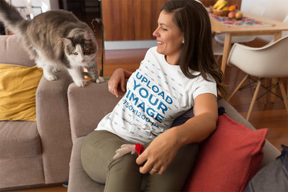 Girl Wearing a T-Shirt Mockup While her Cat Walks on the Sofa a18967