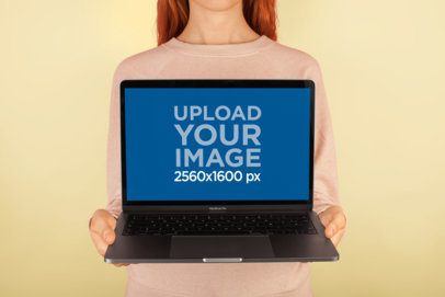Mockup of a Girl Holding a MacBook In Front of a Solid Color Wall a20565
