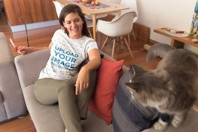 Girl Wearing a T-Shirt Mockup on a Couch with an Angry Cat a18968