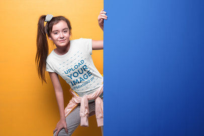 Girl with Ponytail Wearing a T-Shirt Mockup Coming Out of a Wall a19589