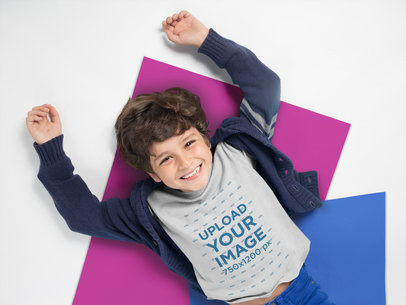 Mockup of a Smiling Kid Wearing a Tshirt Resting Over Pasteboards a19487