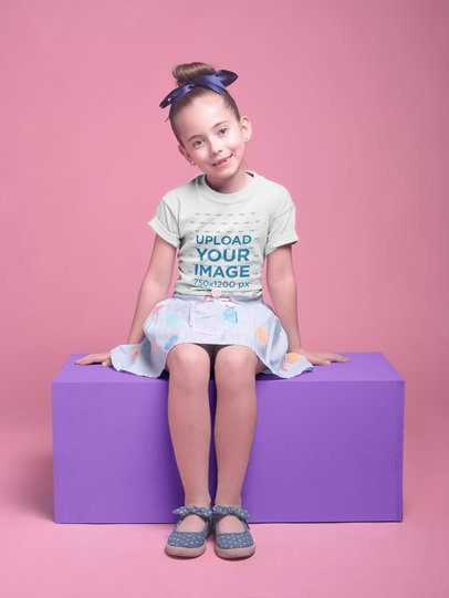 Smiling Girl with a Skirt Wearing a T-Shirt Mockup Sitting on a Block a19730