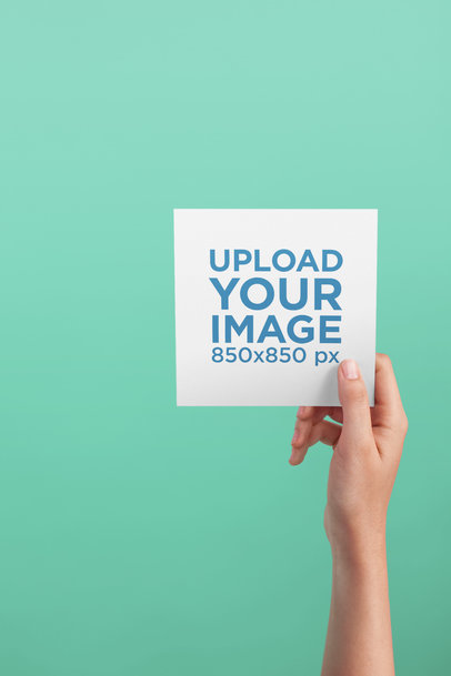 Post Card Mockup Being Held Against a Solid Color Background a20554