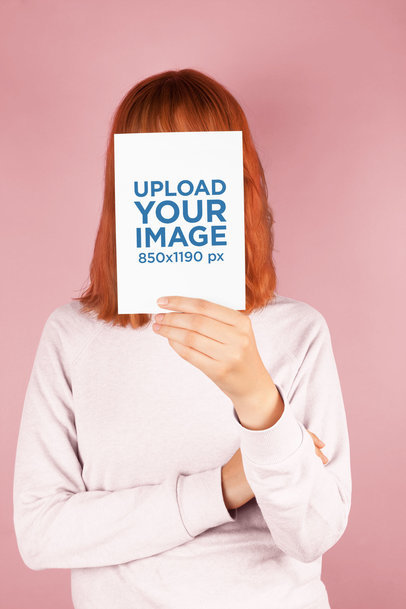 Red-Head Girl Holding a Vertical Postcard Mockup Against her Face a20560