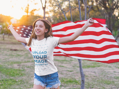Blonde Teen Girl Wearing a T-Shirt Mockup Holding the American Flag Facing the Wind a20707