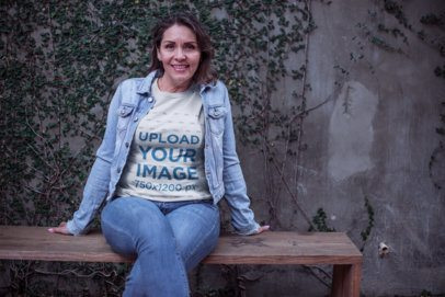 Lady Wearing a T-Shirt Mockup and a Denim Jacket Sitting on a Wooden Bench a20368