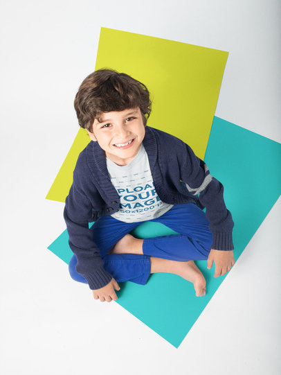 Smiling Kid Wearing a Tshirt Mockup Sitting on Solid Color Pasteboards a19486