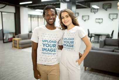 Smiling Interracial Couple Wearing T-Shirts Mockup at the Office a20522
