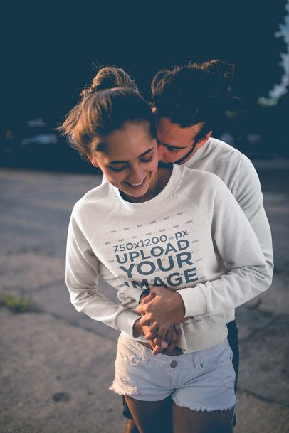 Happy Woman Wearing a Crewneck Sweater Mockup Being Hugged by her Boyfriend a20595