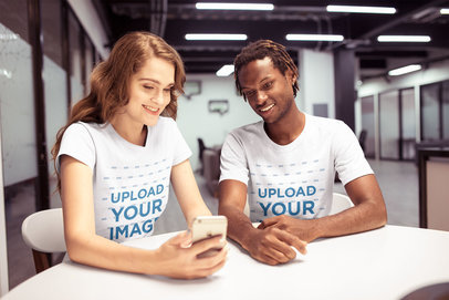 Interracial Pair of Friends Wearing T-Shirts Mockup Watching a Phone a20525