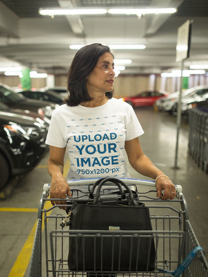 Senior Woman Wearing a Tshirt Mockup Looking for her Car in the Parking Lot a20352