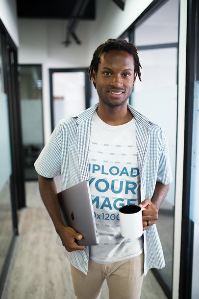 Smiling Black Man Wearing a Tshirt Mockup Holding a Coffee Cup at an Office a20515