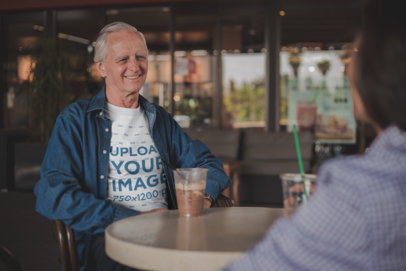 Happy Senior Man Wearing a T-Shirt Mockup Having a Frappuccino with a Friend a20487