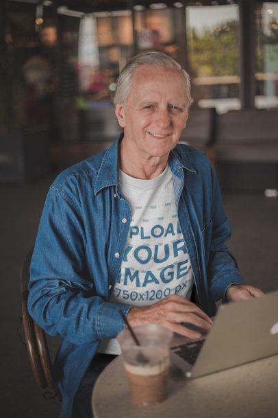 Happy Senior Man Wearing a Tshirt Mockup Working at a Coffee Shop a20507