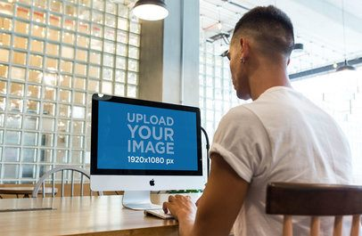 iMac Mockup Being Used by a Man at a Startup a20751