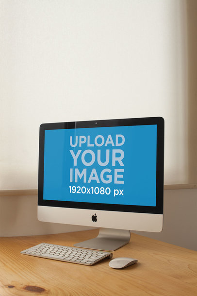 Vertical Shot of an iMac Mockup Standing on a Wooden Desk a20815