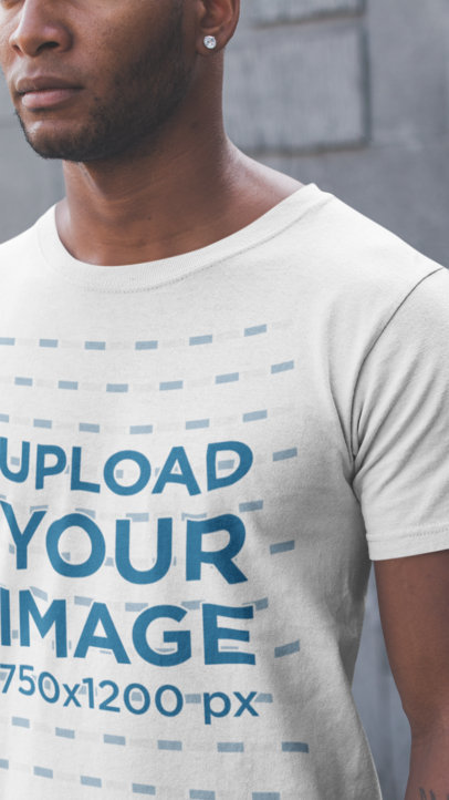 Closeup of a Black Man Wearing a Tshirt Mockup Against a Concrete Wall a20905