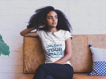 Black Girl with Curly Hair Wearing a Tshirt Mockup Sitting on a Sofa a20395