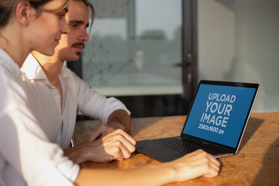 Man and Woman Working with a MacBook Mockup on a Wooden Desk a20986