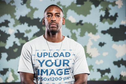 Serious Veteran Wearing a Tshirt Mockup Against a Camo Wall a20921