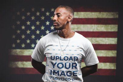 Man Wearing a Tshirt Mockup Standing Against an American Flag a20924