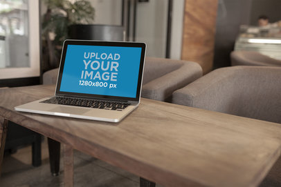 Open MacBook Mockup Standing on a Long Dark Wooden Coffee Table a20997