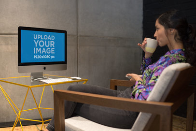 Woman Zipping Tea in Front of an iMac Mockup a21164