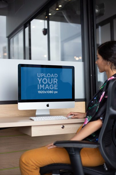 Woman Working on an iMac Mockup on a Wooden Desk a21170
