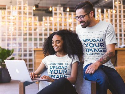 Smiling Coworkers Wearing T-Shirts Mockup while Watching a Laptop a20430