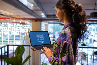 Woman Working with MacBook Mockup Standing Near a Plant a21176