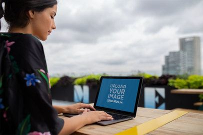 Woman Working with MacBook Pro Mockup on a Terrace a21185