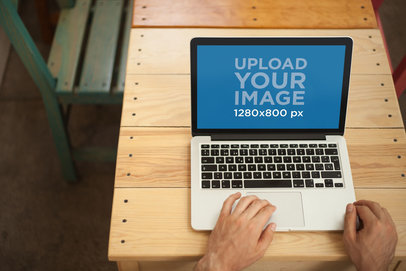 Mockup of a Man Using a MacBook on a Wooden Table a21010
