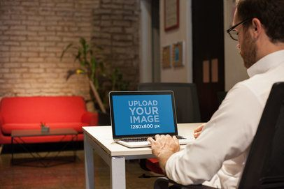 Mockup of a Man Working with a MacBook on a White Table a21004