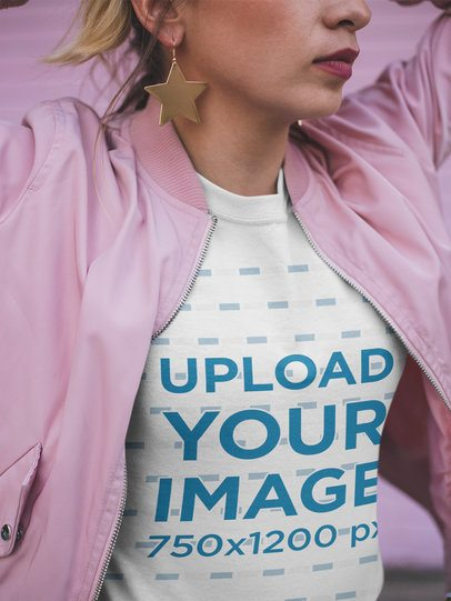 Closeup T-Shirt Mockup of a Woman Wearing a Pink Jacket and Star Earrings a18562