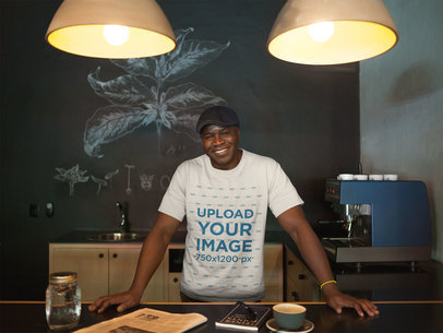 Mockup of a Smiling Black Man Wearing a Round Neck T-Shirt and a Beret at Home a21422