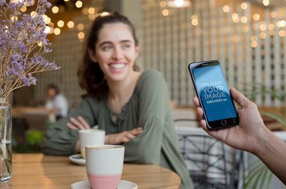 Space Gray iPhone 8 Plus Mockup Featuring a Man with a Girl at a Coffee Shop a21265