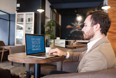 MacBook Mockup Featuring a Man Working while at a Coffee Shop a21012