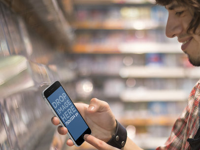 iPhone 6 Mockup Template of Young Man Shopping for Video Games