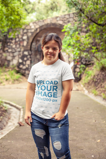 T-Shirt Mockup of a Smiling Girl with Down syndrome Standing Near a Bridge at a Park a21378