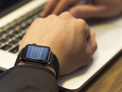 Businessman Typing on Laptop and Using Apple Watch Mockup