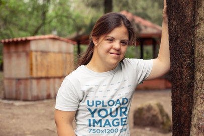 Round Neck Tee Mockup Featuring a Girl Leaning Against a Tree with One Arm a21383
