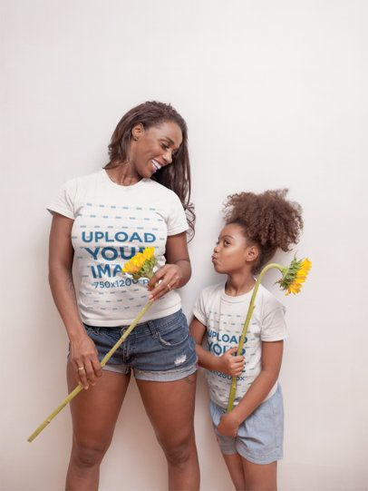 T-Shirt Mockup of a Girl with Curly Hair Holding a Sunflower with her Mom a21330