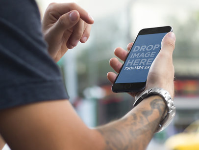 Tattooed Young Man in Urban Setting Using an iPhone 6 Mockup