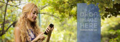 Beautiful Mockup of Blonde Girl Using Her Smartphone Below a Tree