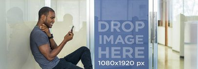 Handsome Young Man Sitting Outside Glass Doors and Using His Smartphone